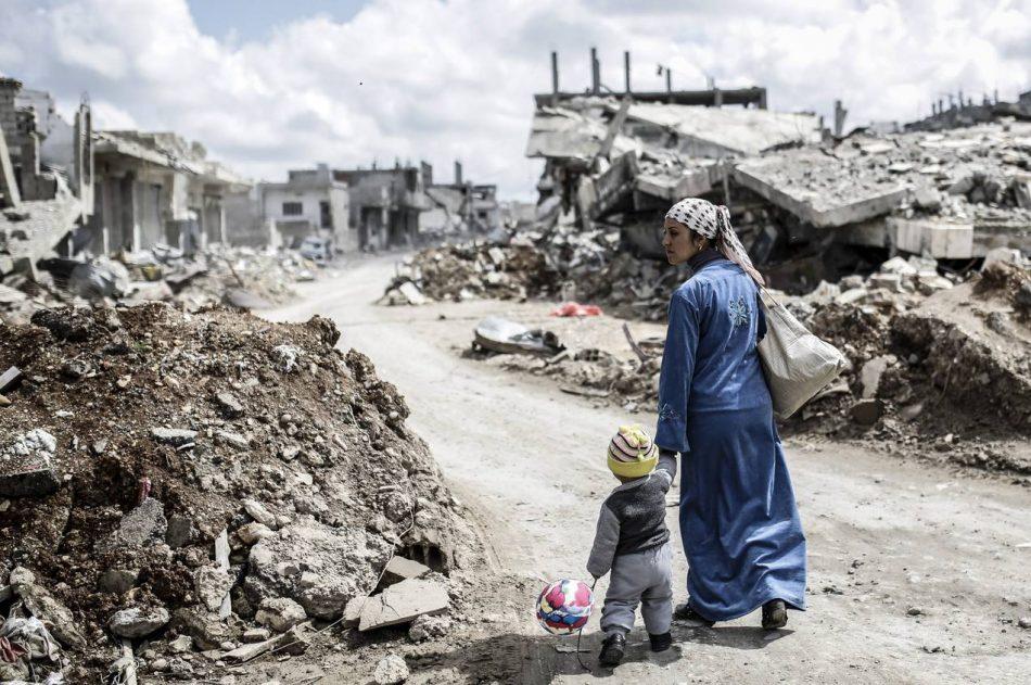 Madre e hijo en medio de los escombros de las bombas en Siria
